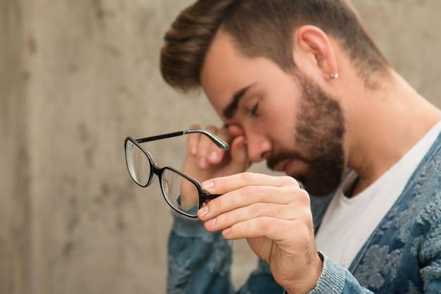 Человек с усталыми глазами после долгой работы Premium Фотографии