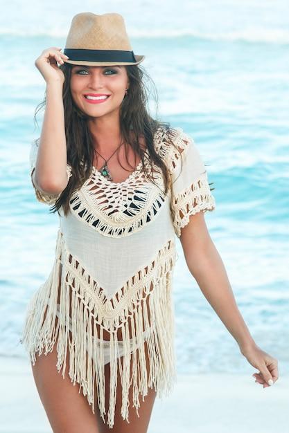 ビーチで帽子をかぶっている美しい女性 Premium写真