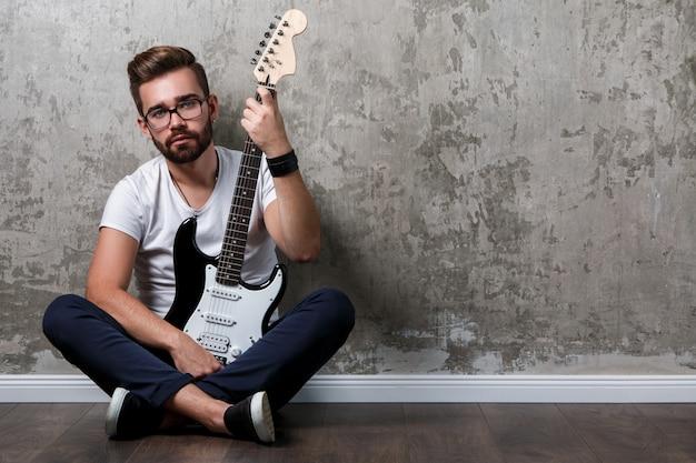 ギターを持つスタイリッシュな男 Premium写真