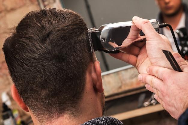 Парикмахер работает с машинкой для стрижки волос Premium Фотографии