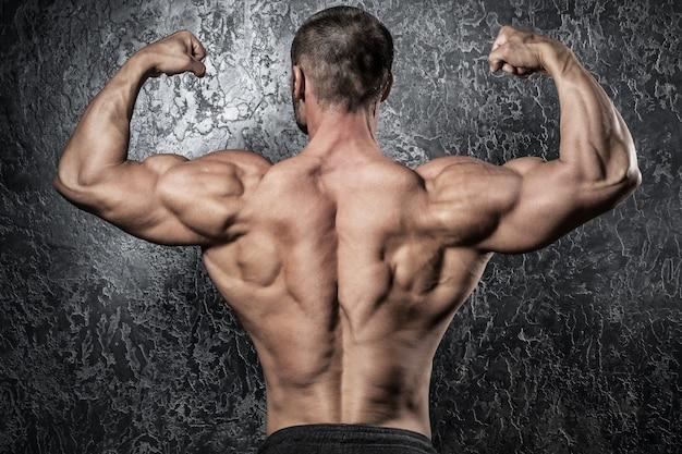 彼の筋肉の背中を示す男 Premium写真