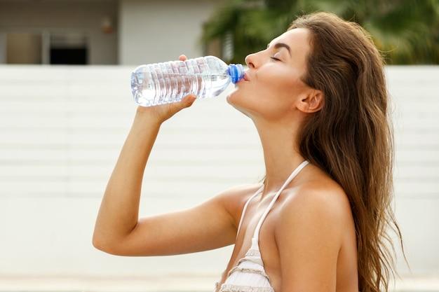 スイミングプールの横にある水のボトルを持つ女性 Premium写真