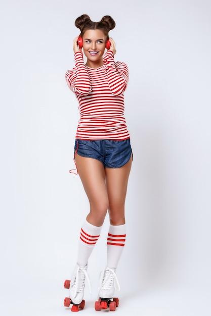 Красивая женщина в роликовых коньках и с красными наушниками Premium Фотографии