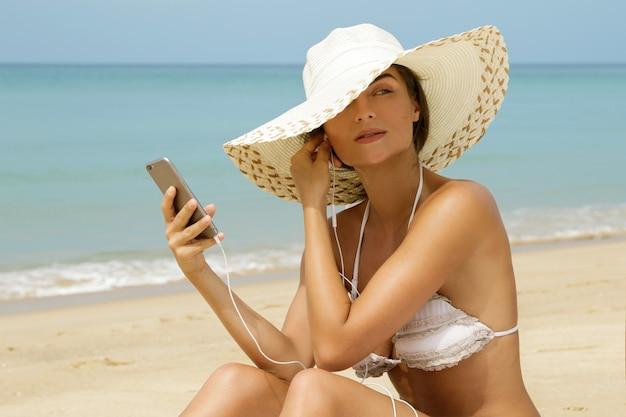 Красивая женщина слушает музыку на пляже Premium Фотографии