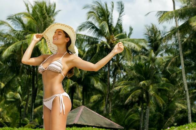Красивая женщина на пляже с пальмами Premium Фотографии