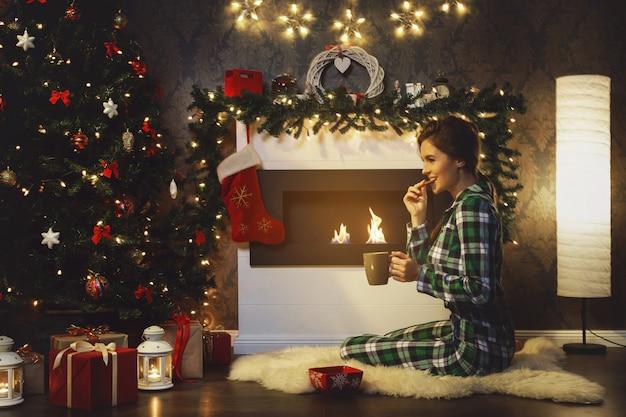 Женщина, сидящая у камина, пьет горячий чай с печеньем Premium Фотографии