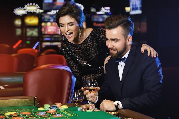 美しく、豊かなカップルがカジノでルーレットをプレイ Premium写真