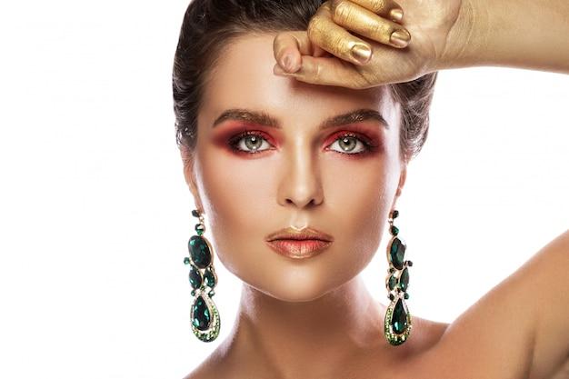 Красивая женщина с красочным макияжем носит серьги с зелеными изумрудами Premium Фотографии