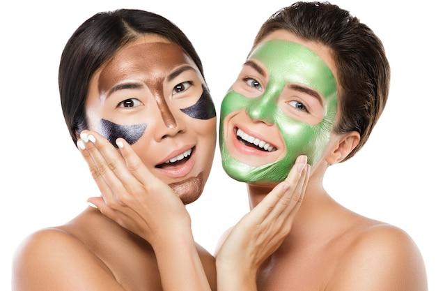 Две красивые девушки с разноцветными отшелушивающими масками на лицах Premium Фотографии