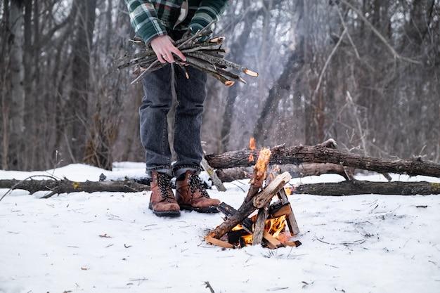 雪に覆われた森でキャンプファイヤーを作る。森の中で冬の日の火の近くの男性人 Premium写真