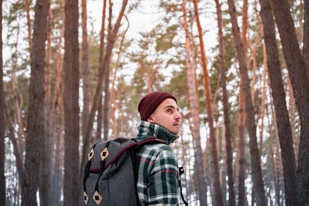 冬の森で男性の人をハイキングします。美しい雪に覆われた森の中を歩いて市松模様の冬シャツの男 Premium写真