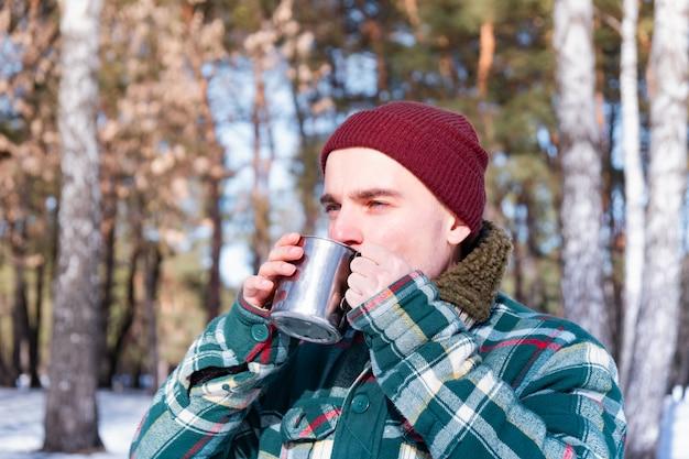 男性は、雪に覆われた冬の森のカップから飲みます。市松模様のシャツを着た男は屋外でコーヒーのカップを保持します Premium写真