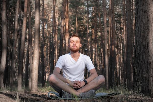 Современный человек сидит в сосновом лесу с закрытыми глазами и наслаждается тишиной природы Premium Фотографии
