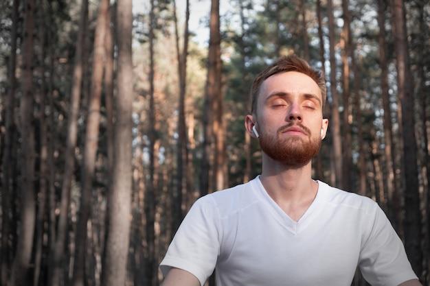 Активный мужчина сидит в сосновом лесу с закрытыми глазами и наслаждается медитацией на природе Premium Фотографии