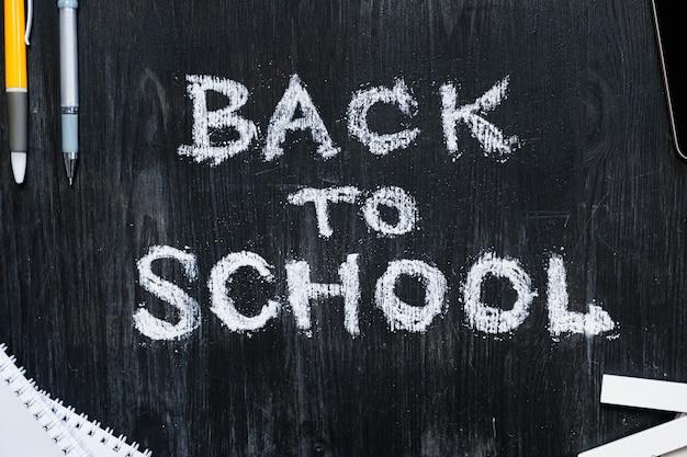 黒い木製黒板に書かれた学校フレーズに戻る Premium写真