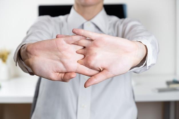 Растягивание рук в редких офисных рабочих местах. руки работника перед современным рабочим столом, концепция выполненной работы Premium Фотографии
