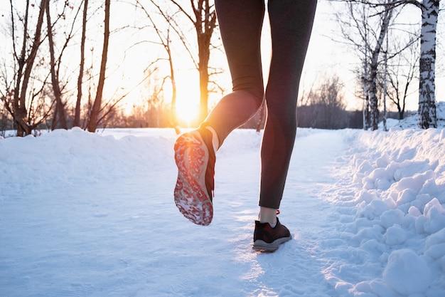 冬のコンセプトで屋外ジョギング。美しい寒い日に雪道に沿って走っている女性の足、レンズフレアで太陽を撃った Premium写真