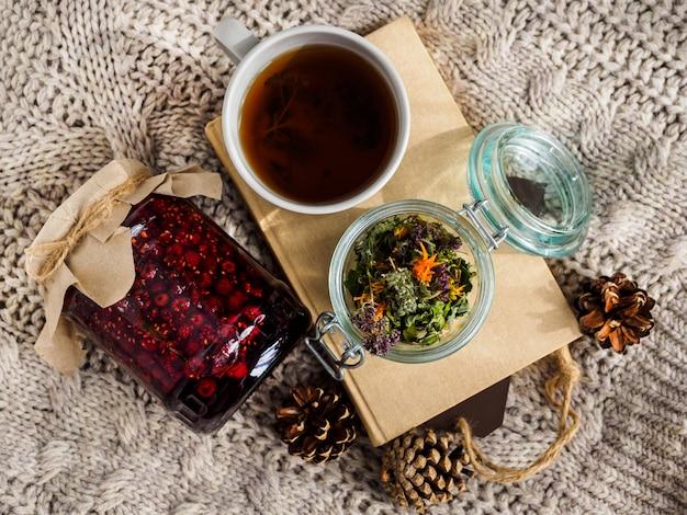 Баночка с малиновым вареньем, чашка чая и книга на шерстяном одеяле. шишки и сухие травы для чая. народная медицина. Premium Фотографии
