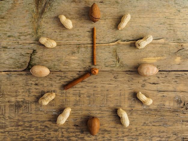 さまざまなナッツとシナモンの木製テーブルで作られた時計 Premium写真