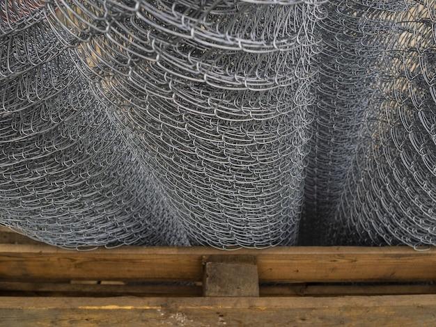 ロールに巻かれたフェンシングの販売。在庫の亜鉛メッキ鋼の格子。大きなセルのあるフェンス Premium写真