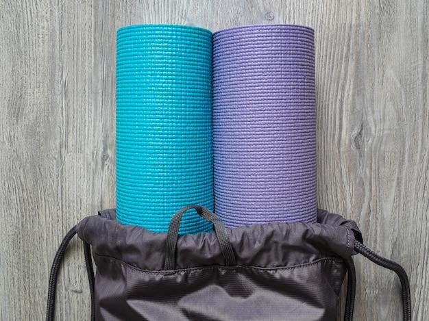 Две коврики для йоги в серую сумку. коврики для пилатеса или фитнеса в тренажерном зале Premium Фотографии