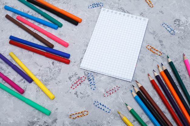色鉛筆、フェルトペン、白いシート、ペーパークリップはグレーの上にあります Premium写真
