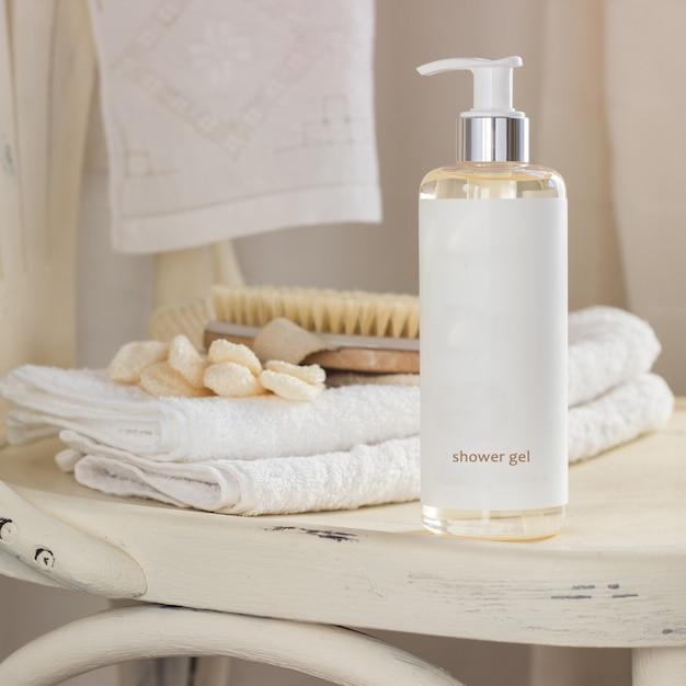 シャワージェル、ボディブラシ、バスルームへの白い椅子のバスミットの入ったボトル Premium写真