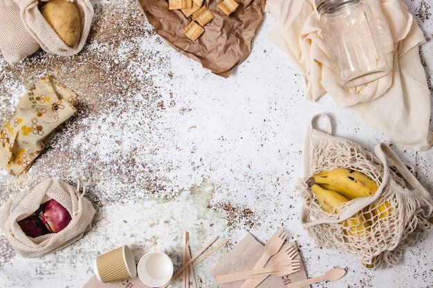 ボウル、皿、グラス、フォーク、ナプキン、さまざまなプラスチック製の無料食器、ショッピングバッグ、ガラスの小さなかん、ミツバチのラップをさまざまな材料、コーヒー、牛乳でテーブルの周りに表示 Premium写真