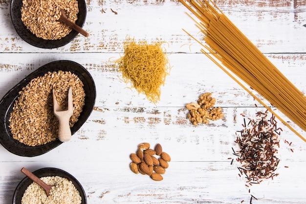 別の種類のボウルに全粒穀物と白いテーブルに広がる Premium写真
