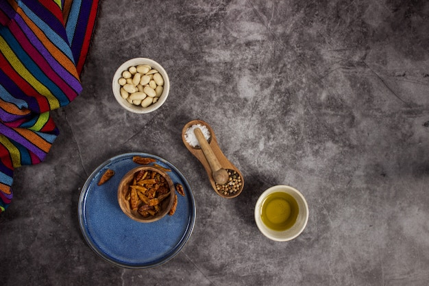 真ん中に配置された黒板にメキシコ料理を準備するためのツリーレッドチリス、ピーナッツ、塩、コショウ、オリーブオイル Premium写真