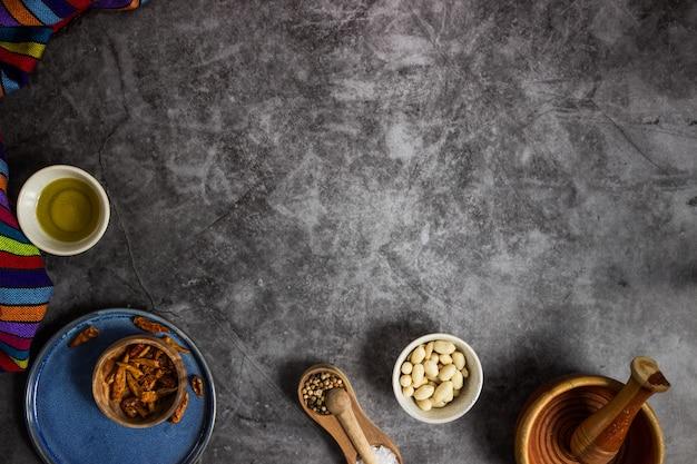 黒板にメキシコ料理を準備するためのツリー赤チリス、ピーナッツ、塩、コショウ、オリーブオイル Premium写真