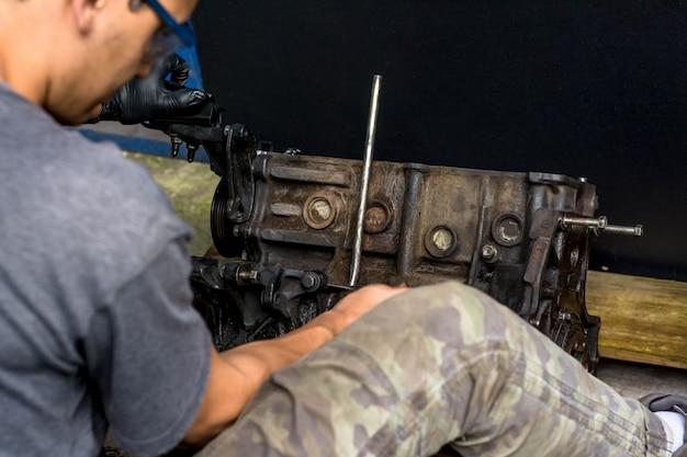 Руки работают в автомобильном двигателе. очистка двигателя автомобиля. механическая мастерская Premium Фотографии