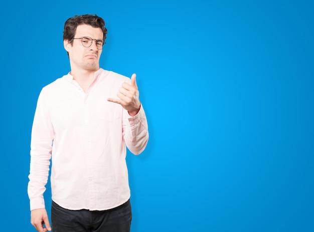 手で呼び出すのジェスチャーを作るためらう若い男 Premium写真