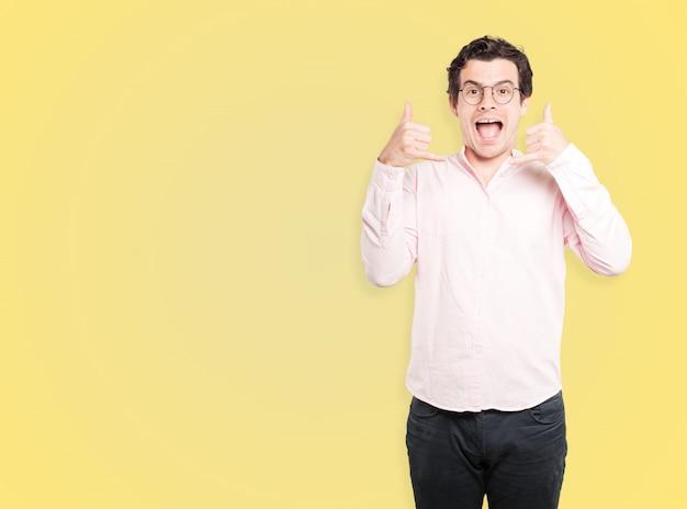 手で呼び出すのジェスチャーを作る驚いた若い男 Premium写真