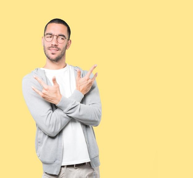 Непослушный молодой человек делает жест рок Premium Фотографии