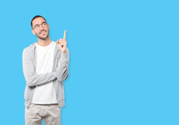Счастливый молодой человек, указывая пальцем Premium Фотографии