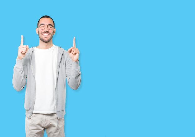 Удивленный молодой человек, указывая пальцем Premium Фотографии