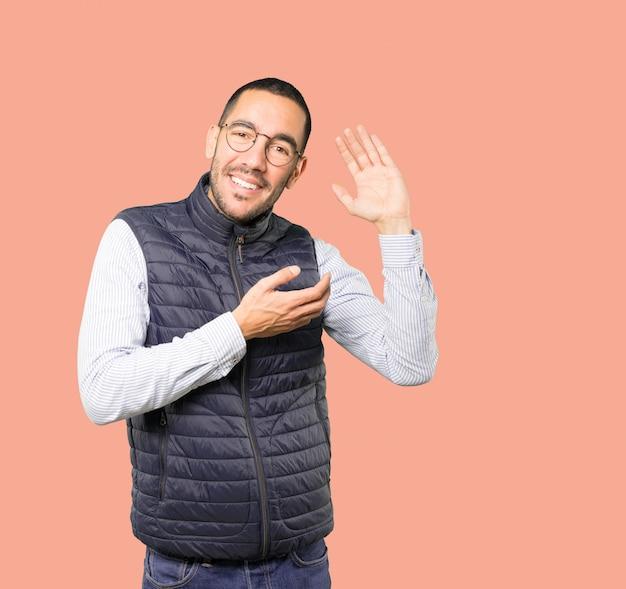 Счастливый молодой человек улыбается и делает жест пытается что-то услышать Premium Фотографии