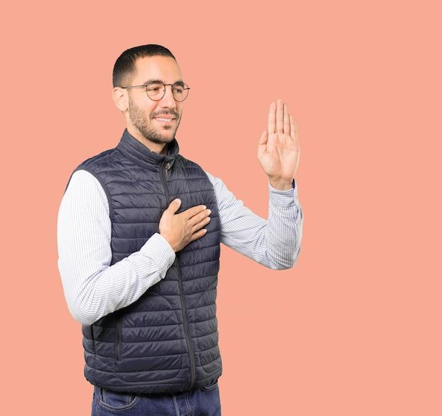 Серьезный молодой человек с жестом клятвы Premium Фотографии