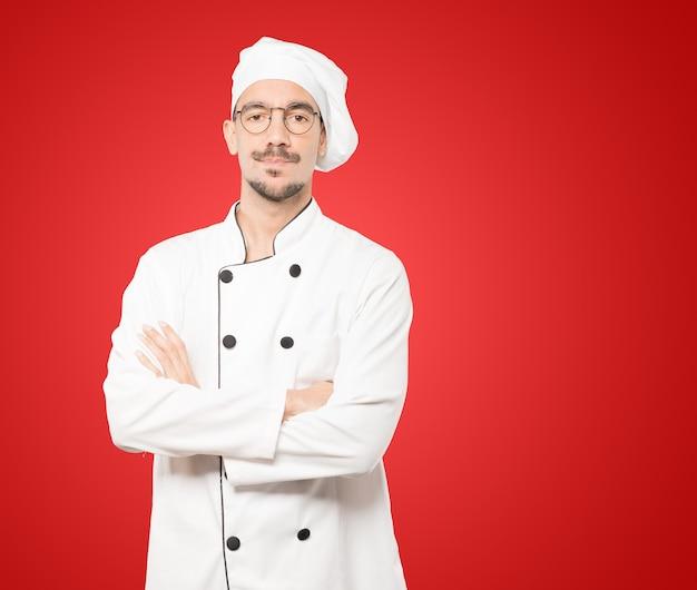 Нерешительный молодой шеф-повар ищет жест Premium Фотографии