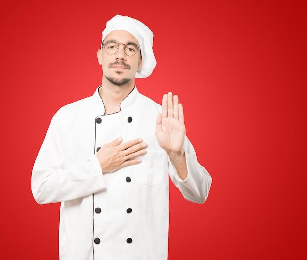 Серьезный молодой повар с жестом клятвы Premium Фотографии