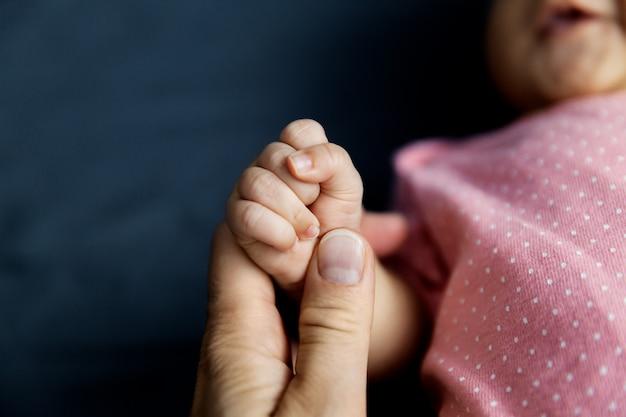 小さな新生児の拳、家族と両親の概念を保持している母親 Premium写真
