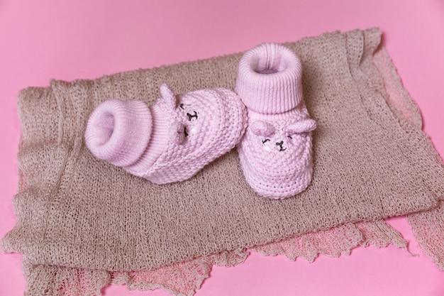 Вязаные крючком новорожденные туфли на розовом фоне ждут девочку Premium Фотографии