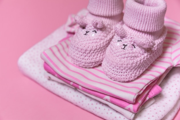 ピンクの背景に新生児の女の子のためのベビー服とかぎ針編みの靴 Premium写真