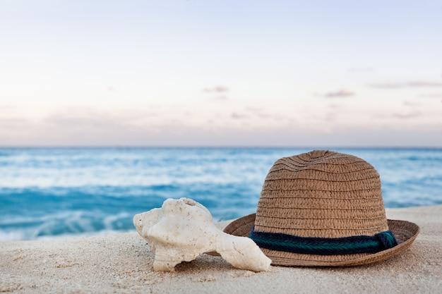 Летняя соломенная шляпа и морские раковины на песчаном пляже на рассвете Premium Фотографии