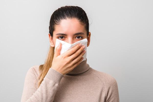 Хватит распространять коронавирус. молодая больная женщина с мухой или вирусом, чихающая и кашляющая в маске или салфетке, выглядит очень безнадежно Premium Фотографии