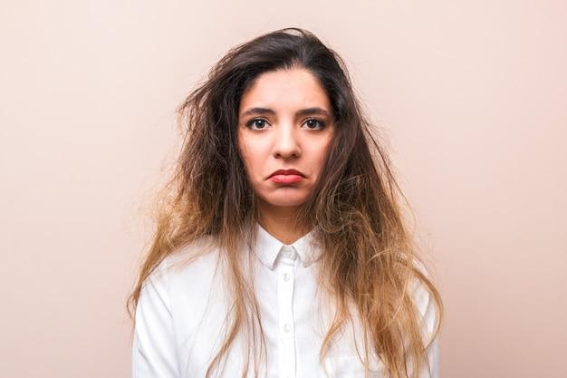 ピンクの背景に白いシャツにもつれた髪の悲しい女。朝の女性のルーチン Premium写真
