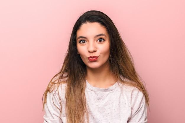 Портрет веселая молодая женщина брюнетка с большими глазами, делая смешное лицо на розовом фоне Premium Фотографии