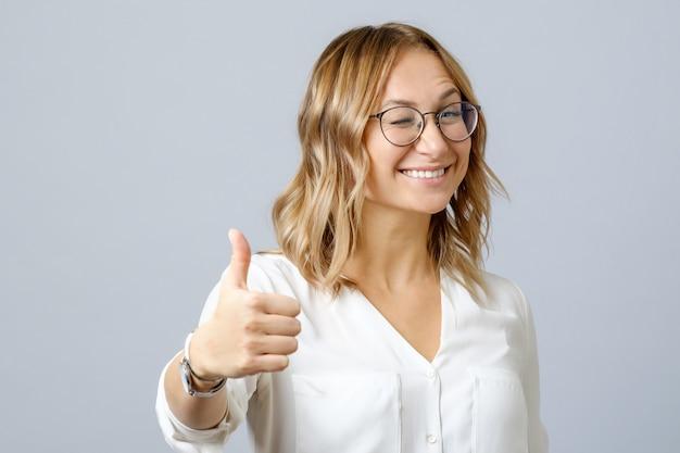 Молодая счастливая усмехаясь жизнерадостная женщина показывая большие пальцы руки вверх Premium Фотографии