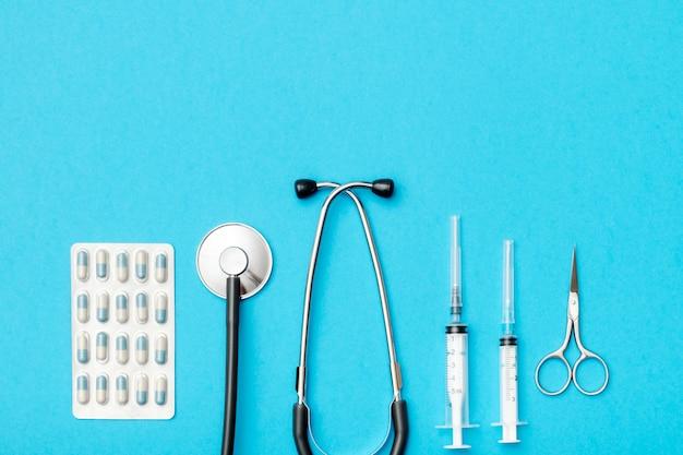 色付きの背景に医療ツールのフラットレイアウト Premium写真